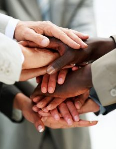 Closeup image of hands of businesspeople on top of each other as symbol of their partnership
